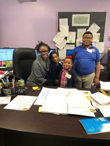 Principal with students sitting at her desk.